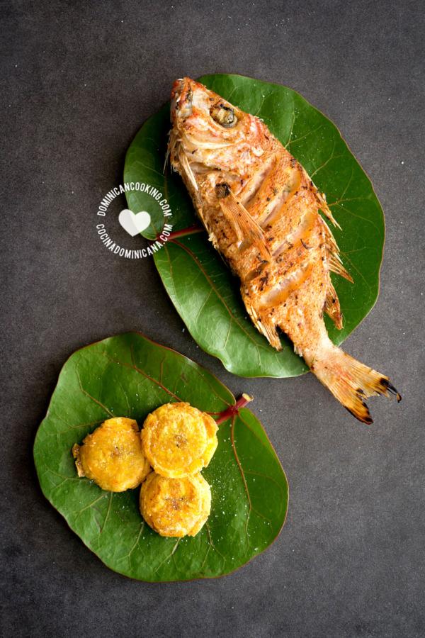 Pescado Frito sobre hojas de uva de playa, con tostones