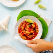 Plato de lambí guisado con mano agarrandolo, al lado, arroz y tostones